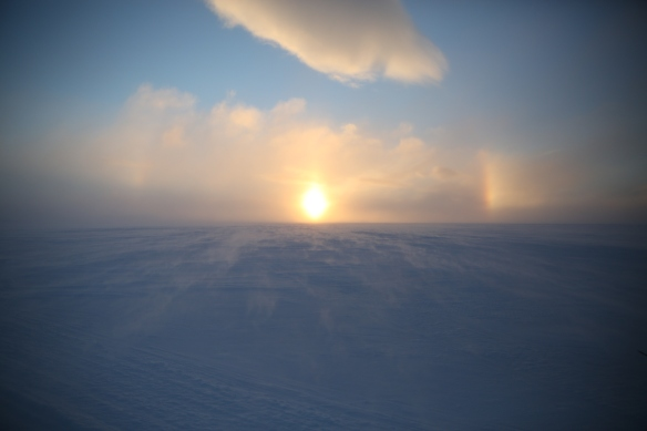 The sun sets over the horizon. The frozen sea seen here is the infamous Northwest Passage.